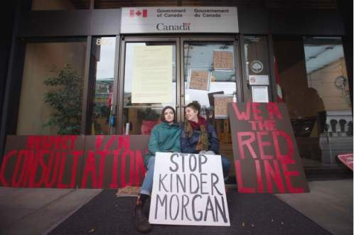 Two women sit outside the offices of the National Energy Board after locking themselves to the doors by placing bike locks around their necks, to protest the Kinder Morgan Trans Mountain Pipeline expansion, in Vancouver, B.C., on Monday January 18, 2016.DARRYL DYCK / THE CANADIAN PRESS