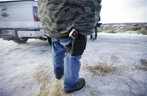 Sean Anderson, of Idaho, a supporter of the group occupying the Malheur National Wildlife Refuge, stands by the front gate Wednesday, Jan. 6, 2016, near Burns, Ore. With the takeover entering its fourth day Wednesday, authorities had not removed the group of roughly 20 people from the Malheur National Wildlife Refuge in eastern Oregon's high desert country. (AP Photo/Rick Bowmer)