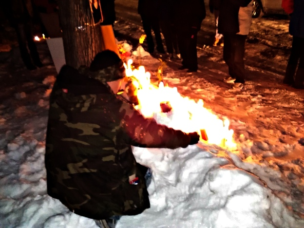 American Indian Movement supporter puts down a candle at the memorial for Mavis Ducharme.