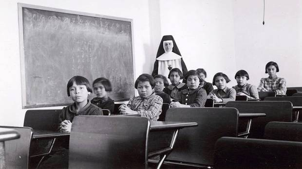 A group of students and a nun pose in a classroom at Cross Lake Indian Residential School in Cross Lake, Manitoba in February, 1940. (HANDOUT/REUTERS)