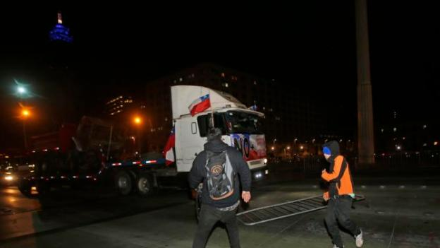 FILE PHOTO: Demonstrators try to stop a caravan of trucks as they drive into Santiago, Chile, Thursday, Aug. 27, 2015.