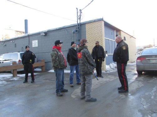 Urban Warrior Alliance members speak to Winnipeg Police Service officers after entering Unicity Taxi offices in protest. (Courtesy Red Power Media)