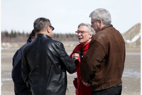 Indigenous Affairs Minister Carolyn Bennett is greeted at the Attawapiskat airport by Chief Bruce Shisheesh as NDP MP Charlie Angus, right, looks on.