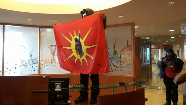 A protester stands on a desk in the Indian and Northern Affairs Canada office Wednesday. Protesters occupied the office to urge Ottawa to address the Attawapiskat, Ont., suicide crisis. (Facebook / Idle No More Toronto)