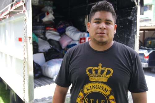One member catches his breath in front of the filled truck with the symbolic Latin King's crown on his T-shirt. Photo:teleSUR