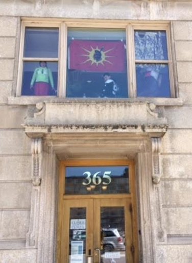 Protesters can be seen in the window of the Indigenous and Northern Affairs office at 365 Hargrave Street in Winnipeg on Thursday. (Dave Gaudet/CBC)