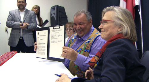 Minister of Indigenous and Northern Affairs Carolyn Bennett signs a memorandum of understanding alongside Manitoba Metis federation president David Chartrand. The document outlines the Liberal government's intention to finally fulfill a land deal from 1870.