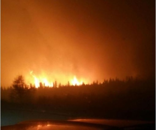 Flames are visible about four kilometres down the road from Noralta Lodge on Monday night. (Name withheld by request)
