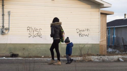 A woman and a young boy walk through the streets in the northern Ontario First Nations reserve in Attawapiskat, Ont. The First Nations community formally requested what is known as an addition to reserve on April 15, days after declaring a state of emergency following multiple cases of youth drug overdoses and suicide attempts. (Nathan Denette/The Canadian Press)