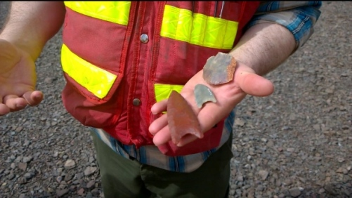 An archaeologist displays casts of artifacts that have been found at the site, including arrowheads that would have been attached to rods to make spears. (Shane Fowler/CBC)