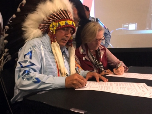 AFN National Chief Perry Bellegarde signs a memorandum of understanding with Indigenous Affairs Minister Carolyn Bennett during the AFN annual general assembly in Niagara Falls, Ont., on July 12, 2016. (Chris Glover/CBC)