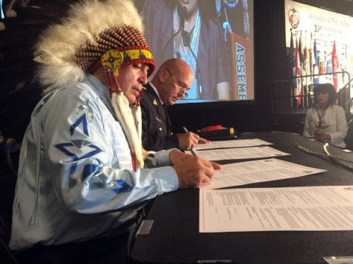 AFN National Chief Perry Bellegarde, left, signs a memorandum of understanding with RCMP Commissioner Bob Paulson, during the AFN annual general assembly in Niagara Falls, Ont., on July 12, 2016. (Chris Glover/CBC)