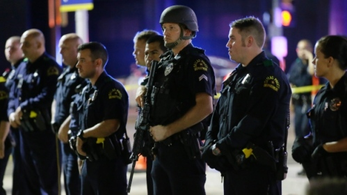 Dallas police officers stand in a line near the site of shootings in downtown Dallas early Friday. (LM Otero/Associated Press)