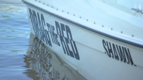 The side of Drag the Red's new boat reads, 'Shawn,' a reference to 18-year-old Kayleen McKay's cousin, Shawn Nepinak, who took his own life by entering the Red River in 2015. (CBC)