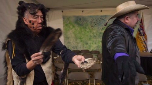 Cecil Grinder, puts purification smoke over Chief Joe Alphonse, Tribal Chairman Tsilhqot'in Nation prior to the start of a ceremony to commemorate the 150th anniversary of six first nation chiefs being hung to death in Quesnel, B.C., on Sunday, Oct. 26, 2014. (THE CANADIAN PRESS/Jonathan Hayward)