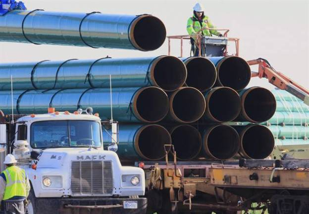 Workers unload pipes for the proposed Dakota Access oil pipeline / AP