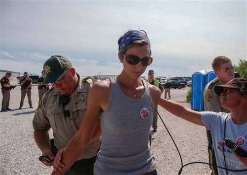 Julia Slocum of Ames, Iowa, is placed under arrest on trespassing charges by a member of the Boone County Sherrif's Department on Wednesday, Aug. 31, 2016, in Boone, Iowa. People gathered to voice their opinion against the development of the Bakken Pipeline during a rally on four of the entrances to the pipeline construction site. The Des Moines Register via AP Bryon Houlgrave