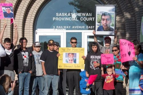 Family, friends and supporters for Colten Boushie hold signs during a rally outside of the Saskatchewan Provincial Court in North Battleford,Thursday, August 18, 2016. People rally outside a Saskatchewan courthouse Thursday where a farmer accused of fatally shooting a First Nations man is to make an appearance. (THE CANADIAN PRESS/Liam Richards)