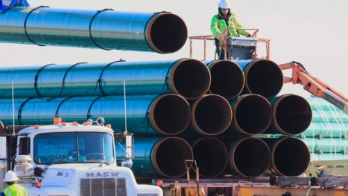 Workers unload pipes for the proposed Dakota Access oil pipeline that would stretch from the Bakken oil fields in North Dakota to Illinois. (Nati Harnik/Associated Press)
