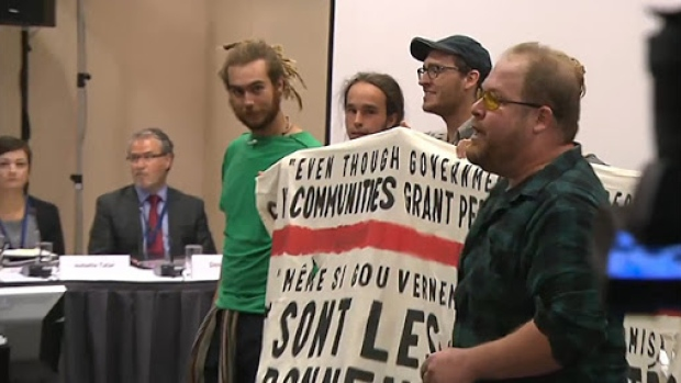 Protesters unfurled an anti-Energy East banner after disrupting the National Energy Board proceedings in Montreal. (CBC)