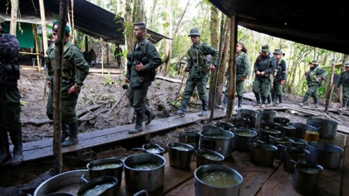 Members of the 51st Front of the Revolutionary Armed Forces of Colombia stand in line to get food at a camp in Cordillera Oriental, Colombia. Credit: Reuters