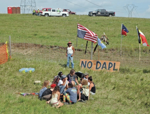 Bill Left Hand, of McLaughlin, South Dakota, stands next to a sign at the site of a protest Friday, Aug. 12, against construction of the Dakota Access Pipeline.