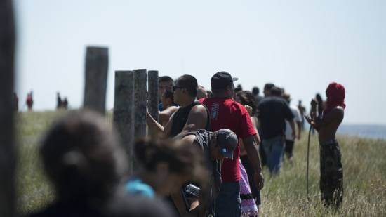 File photo of protesters of the Dakota Access Pipeline looking over a fence on top of a hill on the west side of the Missouri River at pipeline construction crews as they work on the other side of the river on Aug. 16, 2016. Christopher Juhn for MPR News File