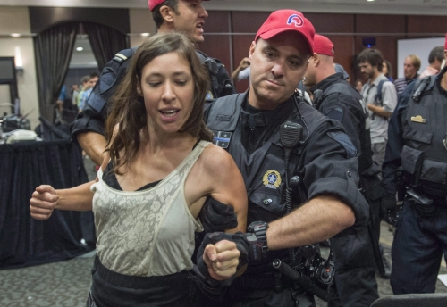 Alyssa Symons-Bélanger is detained by police following protest at National Energy Board hearings on the Energy East pipeline in Montreal on Aug. 29, 2016. Photo by The Canadian Press.
