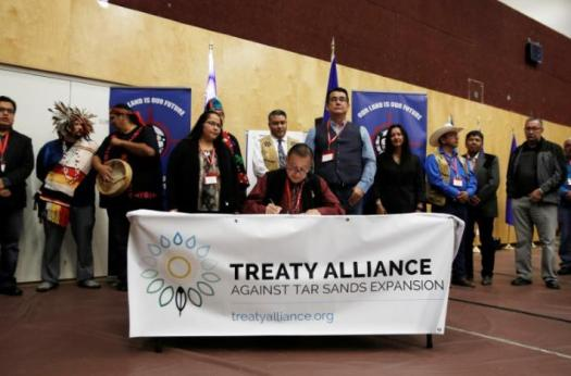 Grand Chief Stewart Phillip signs the Treaty Alliance Against Tar Sands Expansion with other First Nations leaders during an announcement on oil sands pipelines, with special relevance for the Kinder Morgan and Northern Gateway proposals, at the Musqueam Community Centre in Vancouver, British Columbia, Canada, September 22, 2016. REUTERS/Ben Nelms