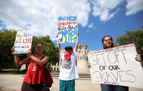 Protesters hold signs outside the U.S. District Court in Washington, where a hearing was being held to decide whether to halt construction of an oil pipeline in parts of North Dakota where a Native American tribe says it has ancient burial and prayer sites, September 6, 2016. REUTERS/Kevin Lamarque