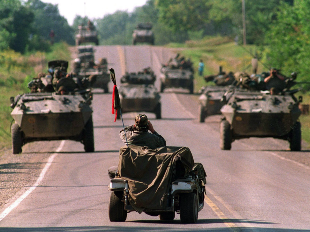 A Mohawk Warrior in a golf cart watches approaching Canadian army armoured vehicles during the 1990 Oka crisis.