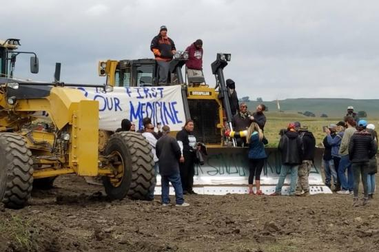 Pipeline protesters standing on vandalized construction equipment in North Dakota. Photo source: Morton County