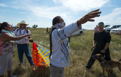 A Native American protester holds up his arms as he and other protesters are threatened by private security guards and guard dogs, at a work site for the Dakota Access Pipeline (DAPL) oil pipeline, near Cannonball, North Dakota, September 3, 2016. Hundreds of Native American protestors and their supporters, who fear the Dakota Access Pipeline will polluted their water, forced construction workers and security forces to retreat and work to stop. / AFP PHOTO / Robyn BECKROBYN BECK/AFP/Getty Images ROBYN BECK / AFP - Getty Images