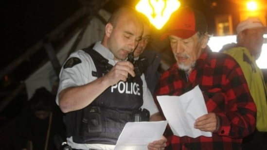 A police officer speaks to Innu leader Bart Jack, one of the people protesting at the Muskrat Falls gates. (Mark Quinn/CBC)