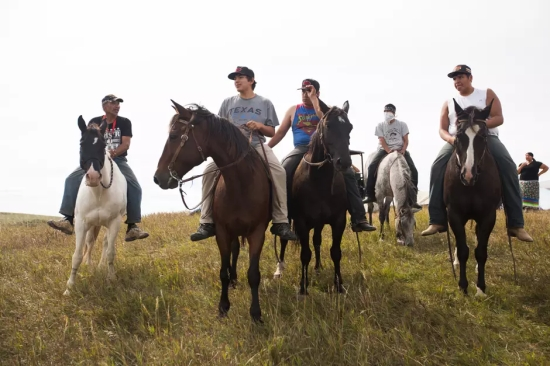 Riders of all ages gather on the hilltop at Sacred Stone Camp near Cannonball