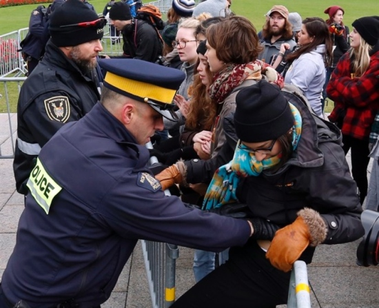 A protester is detained by Parliamentary Security and the RCMP after she attempted to go through a barrier during a demonstration on Parliament Hill, Monday October 24, 2016 in Ottawa. THE CANADIAN PRESS/Fred Chartrand