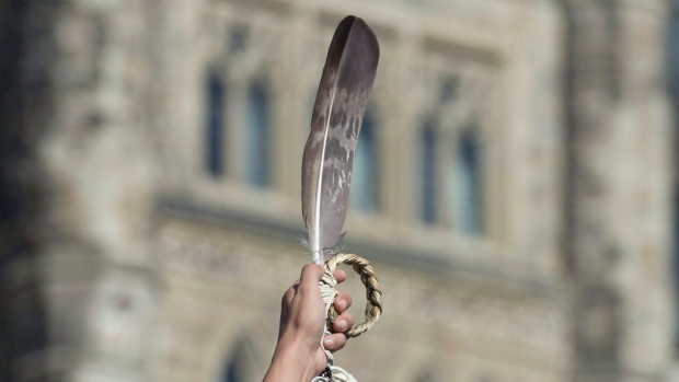 An eagle feather, an Indigenous symbol, is held up on Parliament Hill. The Algonquins of Ontario are one step closer to assuming tens of thousands of acres of their ancestral territory in a historic treaty. (Adrian Wyld/Canadian Press)