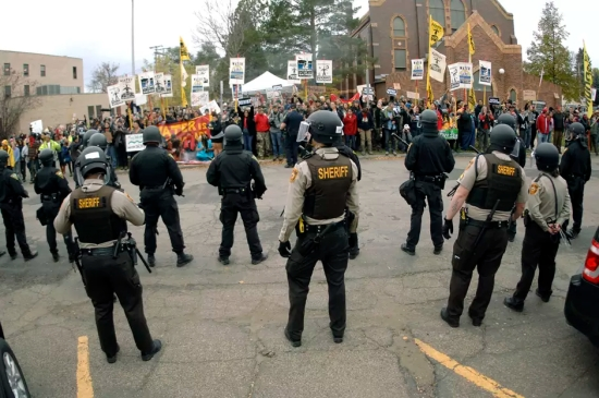Law enforcement officers line the street in front of the Morton County Courthouse in Mandan, N.D., as Dakota Access Pipeline protesters stand on the opposite side of the street on Monday, Oct. 17, 2016.