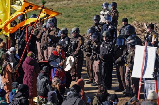 A person with a hand drum paces between law enforcement officers and a line of protesters along a highway in North Dakota. (Tom Stromme/The Bismarck Tribune)