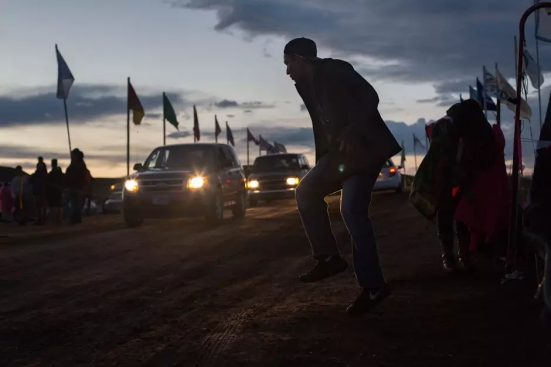 "Tyler Fourth, a Standing Rock Sioux, dances while working a checkpoint at Sacred Stone Camp near Cannonball, ND on Friday, September 9, 2016. Fourth is cautiously optimistic about the situation but has no intention of leaving yet, saying ""it's not over till it's over."""