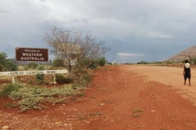 Man walks on a dirt road next to the sign: Welcome to Western Australia PHOTO After walking more than 1,600km, Mr Pryor crossed the WA border.