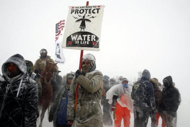 Veterans join activists in a march just outside the Oceti Sakowin camp during a snow fall as 'water protectors' continue to demonstrate against plans to pass the Dakota Access pipeline adjacent to the Standing Rock Indian Reservation, near Cannon Ball, North Dakota, U.S., December 5, 2016. REUTERS/Lucas Jackson