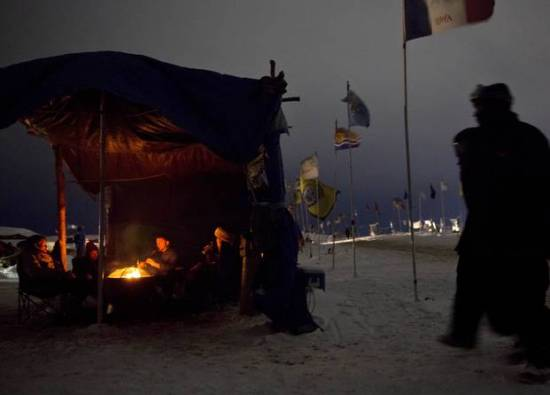 At night, communal sleeping spaces are organized with burning wood stoves.Source: David Goldman/AP
