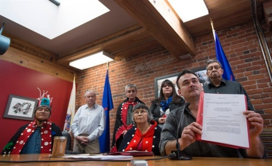 Richard Wright, spokesperson for the Hereditary Chief of Luutkudziwuus, holds up a copy of the fourth federal lawsuit against the Pacific Northwest LNG project during a news conference in Vancouver, Tuesday, Jan.10, 2017. The Gitxsan chiefs announced Tuesday that they have joined other lawsuits in the fight against the Pacific Northwest LNG expansion plans. THE CANADIAN PRESS/Jonathan Hayward