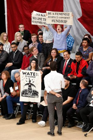 Prime Minister Justin Trudeau speaks with pipeline protestors as they stand and hold signs at a town hall at the University of Winnipeg in Winnipeg, Thursday, January 26, 2017. THE CANADIAN PRESS/John Woods
