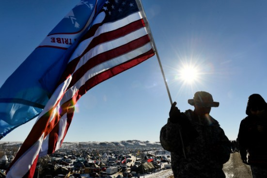 US veterans and Native Americans hold flags on the road near Oceti Sakowin Camp on the edge of the Standing Rock Sioux Reservation on December 4, 2016 outside Cannon Ball, North Dakota. Native Americans and activists from around the country have gathered at the camp to try to halt the construction of the Dakota Access Pipeline.
