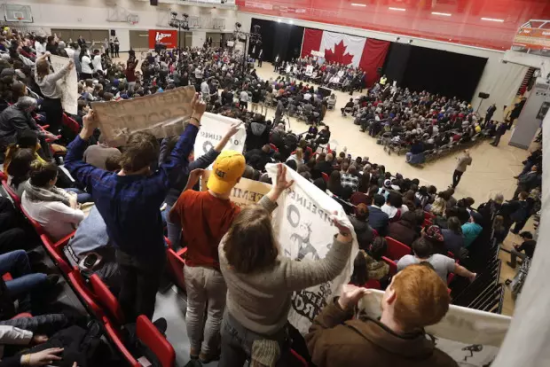 Pipeline protestors stand and hold signs as Prime Minister Justin Trudeau speaks with the public at a town hall at the University of Winnipeg in Winnipeg, Thursday, January 26, 2017.