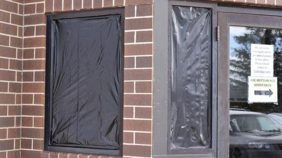 Two windows are covered up Friday morning at the Enbridge building in Bemidji. Police are investigating after shots were fired at the front door and windows of the building. (Maggi Stivers   Bemidji Pioneer)