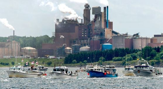 Fishing boats pass the Northern Pulp mill as concerned residents, fishermen and Indigenous groups protest the mill's plan to dump millions of litres of effluent daily into the Northumberland Strait in Pictou, N.S., on Friday, July 6, 2018. (THE CANADIAN PRESS/Andrew Vaughan)
